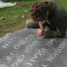 Adam carving a boulder